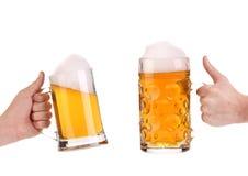 2 полных кружки пива в руке. Стоковые Фото