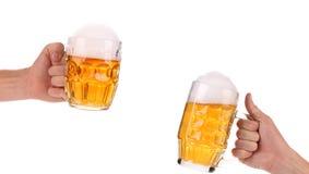 2 полных кружки пива в руке. Стоковое фото RF