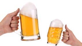 2 полных кружки пива в руке. Стоковое Изображение