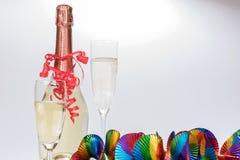 2 полных стекла и бутылки шампанского с красочными гирляндами Стоковая Фотография RF