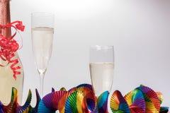 2 полных стекла и бутылки шампанского с красочными гирляндами Стоковые Фотографии RF