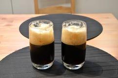 2 полных стекла черного пива на фотографии таблицы Стоковые Изображения RF