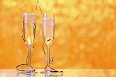 2 полных стекла шампанского с bokeh освещают на заднем плане Стоковая Фотография