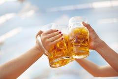 Поднятые глиняные кружки пива провозглашать на Oktoberfest Стоковое Изображение RF
