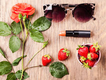 Подняли, солнечные очки, губная помада и клубника стоковое изображение rf