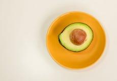 Половина авокадоа зеленая с семенем на плите изолировала предпосылку Стоковые Изображения RF