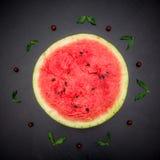Половина арбуза свежего jucie красного на черной предпосылке Стоковые Изображения
