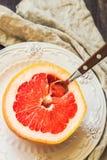 Половина грейпфрута на винтажной плите с ложкой Стоковые Изображения