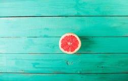 Половина грейпфрута на деревянной предпосылке бирюзы Стоковые Изображения