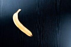 Половина желтого зрелого банана от тропиков на черноте деревянной Стоковые Фотографии RF
