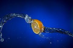 Половина лимона и выплеска воды на голубой предпосылке Стоковое Изображение RF