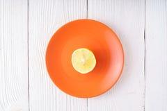 Половина лимона на оранжевой плите Стоковые Изображения