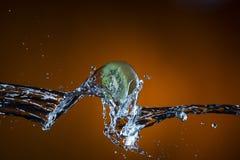 Половина кивиа и выплеска воды на оранжевой предпосылке Стоковое Фото