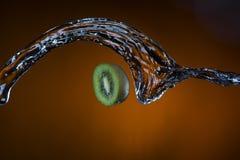 Половина кивиа и выплеска воды на оранжевой предпосылке Стоковое Изображение RF