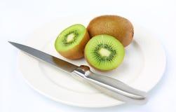Половина сочного плодоовощ кивиа с ножом на белой плите Стоковые Фотографии RF
