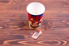 Половинная чашка попкорна, используемого билета на взгляде столешницы Стоковое Фото