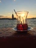 Половинное стекло турецкого чая против башни девушки на заходе солнца внутри Стоковая Фотография RF