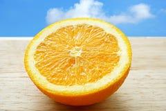Половинный апельсин на деревянном столе, с голубым небом на заднем плане Стоковое фото RF
