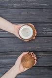 Половинный кокос в женских руках Стоковые Изображения
