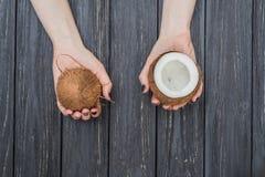 Половинный кокос в женских руках Стоковая Фотография