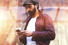 Половинный портрет длины взрослого бородатого человека битника беседуя на телефоне клетки во время идти в городские условия, стоковое фото