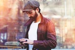 Половинный портрет длины взрослого бородатого человека битника беседуя на мобильном телефоне пока стоящ в городских условиях стоковое фото rf