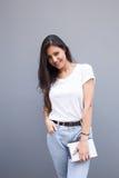 Половинный портрет длины красивой усмехаясь латинской женщины держа ее цифровой планшет пока представляющ для камеры против stre Стоковое Изображение RF