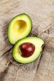 Половины авокадоа на предпосылке мешковины Стоковые Изображения RF