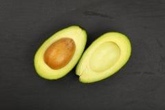 2 половины авокадоа на черной доске шифера Стоковое Изображение