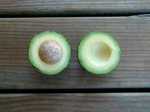 Половины авокадоа с ямой на простой деревянной предпосылке Стоковые Изображения RF