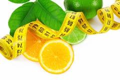 Половины апельсина и известки с измеряя лентой на белизне Стоковая Фотография