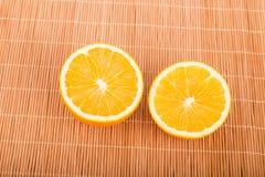 Половины апельсина на бамбуковом Placemat Стоковые Изображения