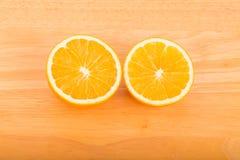 Половины апельсина на деревянной таблице Стоковые Изображения
