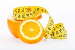 Половины апельсина с измеряя лентой на белой предпосылке Стоковая Фотография RF