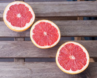 3 половины грейпфрута на деревянной предпосылке Стоковое Фото