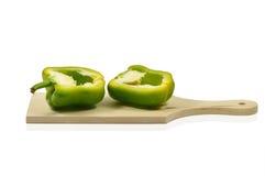 2 половины зеленого перца на деревянной разделочной доске Стоковые Изображения