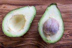 2 половины зрелого авокадоа на деревянной предпосылке Стоковое Изображение RF