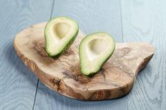 2 половины зрелого авокадоа на разделочной доске над таблицей Стоковые Изображения
