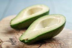 2 половины зрелого авокадоа на разделочной доске над таблицей Стоковое Изображение