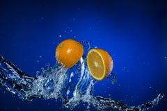 2 половины лимона и выплеска воды на голубой предпосылке Стоковая Фотография