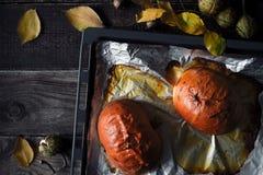 Половины испеченной тыквы на подносе выпечки на взгляд сверху деревянного стола Стоковые Фото