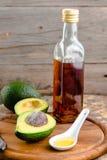 Половины и авокадовое масло авокадоа в стеклянной бутылке на деревянной горжетке Стоковое Изображение