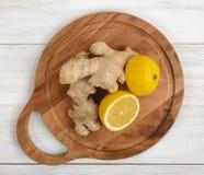 Половины и имбирь лимона клали вне на деревянную разделочную доску Стоковое Фото