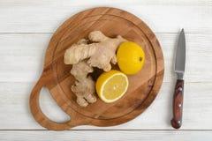 Половины и имбирь лимона клали вне на деревянную разделочную доску Стоковое Изображение RF