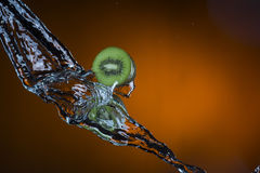 2 половины кивиа и выплеска воды на оранжевой предпосылке Стоковые Изображения