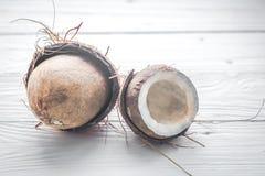 половины кокоса на белой деревянной предпосылке Стоковые Изображения