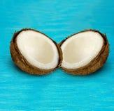 2 половины кокоса на голубой деревянной предпосылке Стоковое Фото