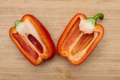 2 половины красного сладостного перца на деревянной предпосылке Стоковое Изображение