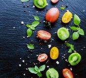 Половины красного цвета и черноты томатов с базиликом листьев зеленого цвета Стоковое Изображение RF