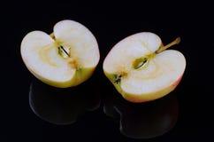 2 половины красного яблока на черной предпосылке Стоковая Фотография